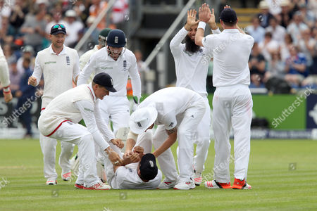 England captain Alastair Cook (on ground) is congratulated by teammates after catching Brad Haddin of Australia at the 2nd attempt off the bowling of Moeen Ali.