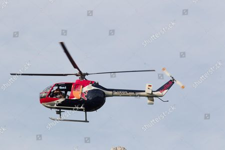 Felix Baumgartner as he pilots the Red Bull helicopter model Bo105 . Austrian Swoop Style competition, world's best pilots at  the lakeside in St. Wolfgan