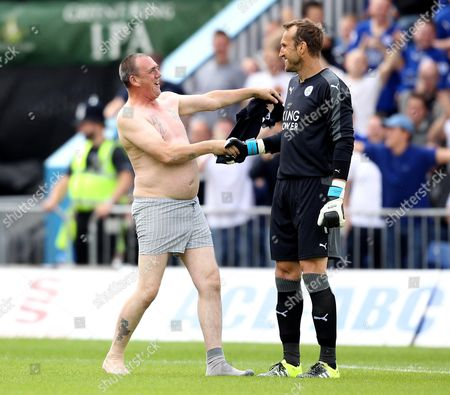 A Leicester City fan invades the pitch and shakes Leicester City's Mark Schwarzer hand