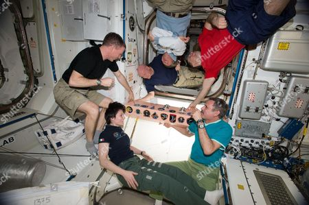 The Expedition 43 crew gathers aboard the International Space Station to affix their mission patch to the vehicle. In view is Commander Terry Virts (center left), Scott Kelly (top left), Gennady Padalka (top center), Anton Shkaplerov (top right), Mikhail Kornienko (bottem right), Samantha Cristoforetti (bottom center)