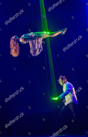Stock Image of Jamie Allan performs a levitation trick with Josephine Wormall at a photocall for 'Impossible' a new magic show opening at the Noel Coward theatre on July 30th