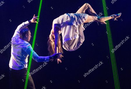 Jamie Allan performs a levitation trick with Josephine Wormall at a photocall for 'Impossible' a new magic show opening at the Noel Coward theatre on July 30th