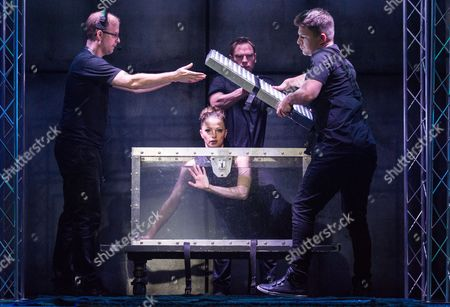 Josephine Wormall is locked in a tank filled with water for a trick with Ali Cook (second right) at a photocall for 'Impossible' a new magic show opening at the Noel Coward theatre on July 30th