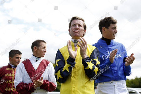 (L-R) Jockeys Andrea Atzeni, Jim Crowley, Pat Cosgrave and James Doyle take part in a minutes applause to celebrate the life of Sir Peter O' Sullevan who recently died before the 14.00; The Land Rover Stakes Race run at Godwood Racecourse on the 3rd Day of The Qatar Goodwood Festival Meeting.