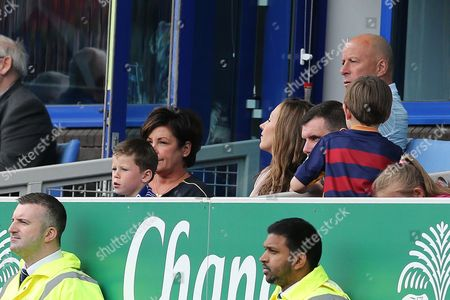 Stock Picture of Kai Rooney watches the match sitting on the knee of Colette McLoughlin from an executive box in the stand