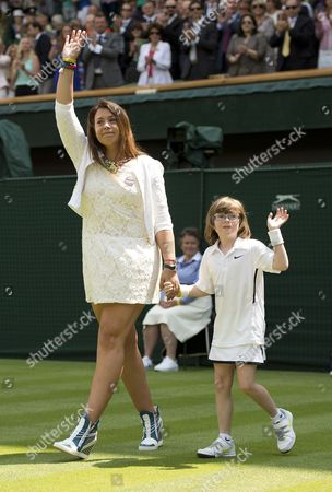 Stock Image of Wimbledon Tennis Championships 2014 Marion Bartoli Sheds A Tear As She Returns To The Scene Of Her Victory In 2013 With Elle Robus-miller A Young Tennis Player From The Elena Baltacha Academy Of Tennis  24/06/2014.