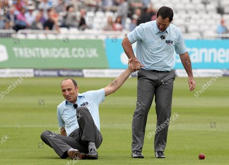 Nasser Hussain is helped up by colleague Ricky Ponting after dropping a catch during a slip fielding demonstration for Sky TV before the start of play