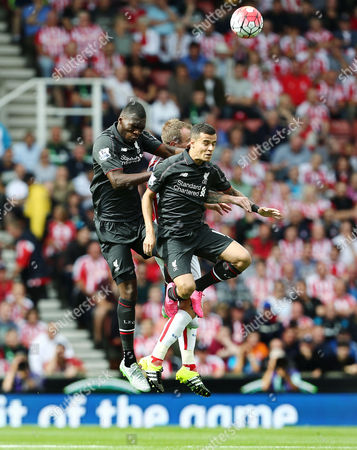 Christian Benteke and Philippe Coutinho of Liverpool jump for a header with Glenn Whelan of Stoke City during the Barclays Premier League match between Stoke City and Liverpool played at the Britannia Stadium, Stoke