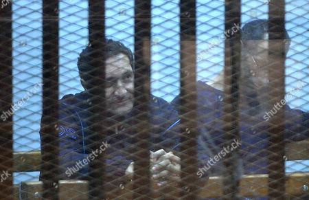 Alaa and Gamal Mubarak, sons of former President Hosni Mubarak sit in a courtroom cage during their trial in Cairo