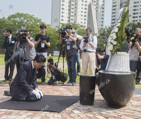Japan's former Prime Minister Yukio Hatoyama bows in front of a memorial stone