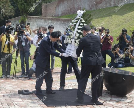 Japan's former Prime Minister Yukio Hatoyama (L) lays a wreath in front of a memorial stone