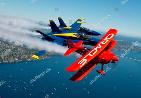 Stock Image of Lead solo Lt. Cmdr. Mark Tedrow and opposing solo Lt. Ryan Chamberlain, assigned toi the U.S. Navy flight demonstration squadron, the Blue Angels, fly alongside Team Oracle air show pilot Sean Tucker while practicing for the Seafair Air Show. Seattle, America