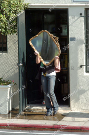 Charlize Theron evading photographers by hiding behind a mirror