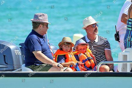 Sir Elton John, David Furnish and their children Zachary Furnish-John and Elijah Furnish-John arrive at Club 55 beach