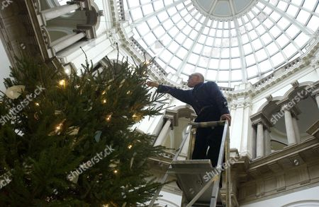 Sculptor Richard wentworth puts the finishing touches to the tree on display at the Tate Britain gallery. Visitors are invited to interact with the tree, leaving digital presents (texts, movies etc) via the bluetooth antenna. The artwork with be auctioned for children's charity 'Artwork'