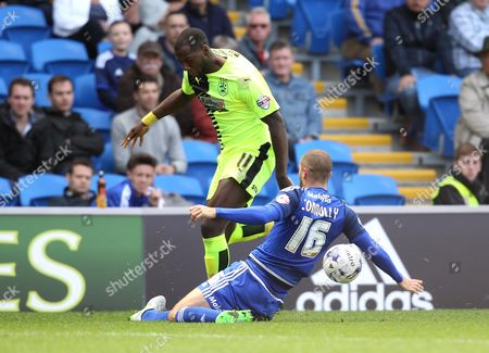 Ishmael Miller of Huddersfield Town is tackled by Matthew Connolly of Cardiff City