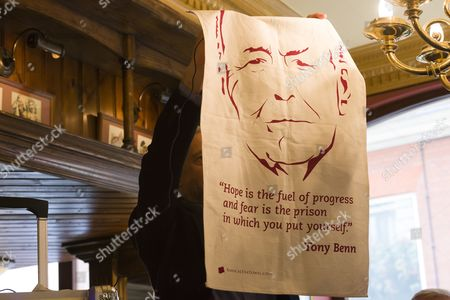 Stock Photo of Jeremy Corbyn holds a tea towel with a quote by Tony Benn on it