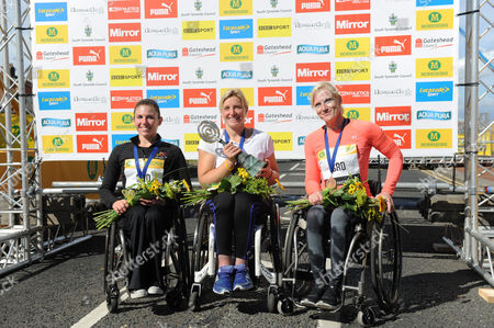 Stock Image of Shelly Woods winner of the Wheelchair Womens Race (centre) poses with second place Amanda McGrory (left) and Margriet Van Den Broek at the podium during the Morrisons Great North Run 2015 at South Shields
