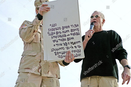 With the help of cue cards held by an Army soldier, David Letterman delivered his opening monologue written specifically for the troops during 'The Late Show' at Camp Taqaddum, Iraq, December 24, 2004. Letterman, along with his musical director Paul Shaffer and stage manager Biff Henderson, brought the popular late night television show to the Marines, sailors and soldiers currently stationed at Camp Taqaddum, Iraq. They were followed with a performance from 'Off the Wall' a southern California band, which added to the holiday festivities.