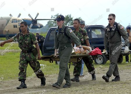 Lieutenant Lisa Peterson, centre, Lieutenant Mark Banks, and two Indonesian Army personnel carrying a patient on a stretcher flown in by a U.S. Navy helicopter to a temporary triage site in Aceh, Sumatra. Medical teams from USS Abraham Lincoln (CVN 72), Carrier Air Wing Two (CVW-2) and the International Organization for Migration (IOM) set up a triage site located on Sultan Iskandar Muda Air Force Base, in Banda Aceh, Sumatra. The two teams worked together with members of the Australian Air Force to provide initial medical care to victims of the Tsunami stricken coastal regions - 02 Jan
