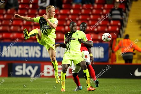 Ishmael Miller of Huddersfield Town and Naby Sarr of Charlton Athletic battle for possession as Kyle Dempsey of Huddersfield Town misses a header