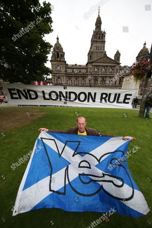 Pro-independence supporter Kes Irving, from Elderslie, poses with a 'Yes' flag in front of a 'End London Rule' banner in the gardens of George Square, Glasgow