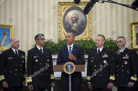 United States President Barack Obama is flanked by Capt. Dan Beck, Deputy Commander of the PHS CC Ebola Response (left) Vice Admiral Vivek M. Murthy, United States Surgeon General (second from left) Rear Admiral Boris Lushniak Officer-in-Charge of MMU Transition Between Teams (second from right) and Rear Admiral Scott F. Giberson, Commander of the PHS CC Ebola Response (right) as he meets with members of the Public Health Service Commissioned Corps (PHS CC) after signing a citation awarding the Presidential Unit Citation to PHS CC members who participated in the Ebola containment efforts in West Africa, in the Oval Office at The White House in Washington, D.C., U.S.,.