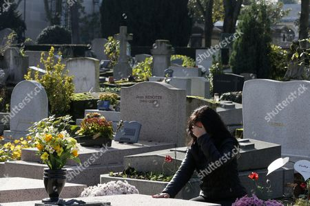 Woman praying at a grave in a cemetery.