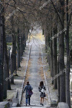 Couple walking in a cemetery in winter.