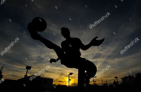 The sun sets behind the Dennis Bergkamp statue during the UEFA Champions League Group F match between Arsenal and Olympiakos played at The Emirates, London on September 29th 2015