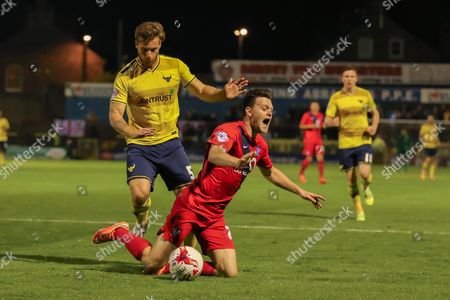 York City forward Reece Thompson falls in the box with close attention from Oxford United defender Johnny Mullins  during the Sky Bet League 2 match between York City and Oxford United at Bootham Crescent, York