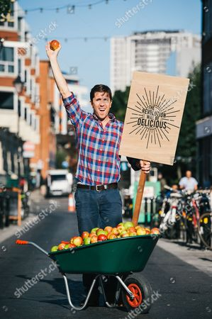 Stock Picture of Farmdrop founder Ben Pugh handing out apples