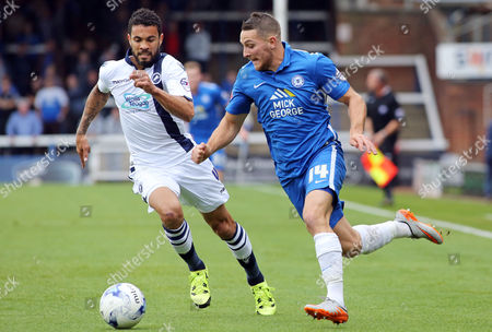 Conor Washington of Peterborough United gets away from Carlos Edwards of Millwall