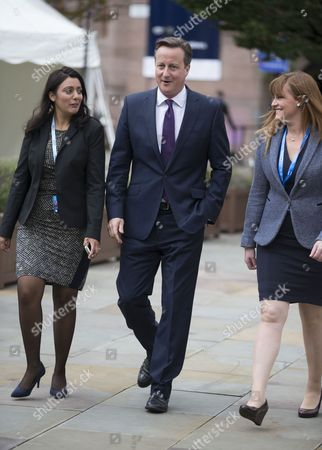 Prime Minister David Cameron with Kelly Tolhurst (L) and Nusrat Ghani (R)arrives to hear Chancellor George Osborne make his speech.