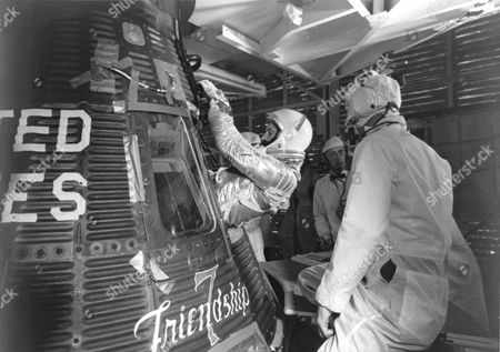 Stock Picture of Astronaut John H. Glenn Jr. enters his Mercury capsule, 'Friendship 7' as he prepares for launch of the Mercury Atlas rocket. On February 20, 1962 Glenn lifted off into space aboard his Mercury Atlas 6 ( MA - 6 ) rocket and became the first American to orbit the Earth. After orbiting the Earth 3 times, Friendship 7 landed in the Atlantic Ocean 4 hours, 55 minutes and 23 seconds later, just East of Grand Turk Island in the Bahamas. Glenn and his capsule were recovered by the Navy Destroyer Noa, 21 minutes after splashdown.