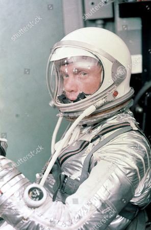 Astronaut John H. Glenn Jr. dons his silver Mercury pressure suit in preparation for launch. On February 20, 1962 Glenn lifted off into space aboard his Mercury Atlas ( MA - 6 ) rocket and became the first American to orbit the Earth. After orbiting the Earth 3 times, Friendship 7 landed in the Atlantic Ocean 4 hours, 55 minutes and 23 seconds later, just East of Grand Turk Island in the Bahamas. Glenn and his capsule were recovered by the Navy Destroyer Noa, 21 minutes after splashdown.