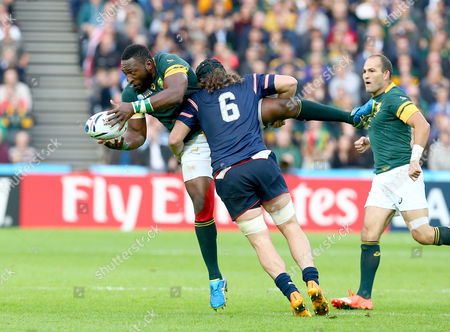 """Tendai Mtawarira (""""The Beast"""") of South Africa is lifted in the tackle by Daniel Barrett of the USA."""
