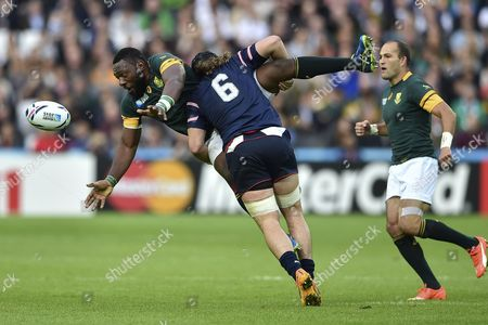 Tendai Mtawarira of South Africa offloads the ball after being tackled by Daniel Barrett of the USA
