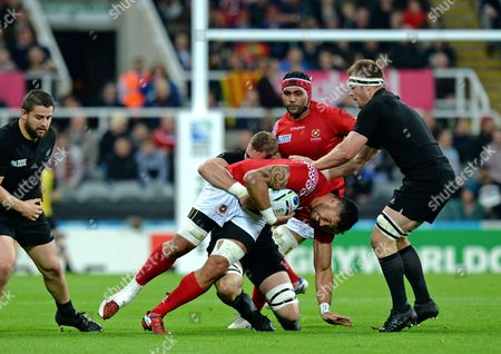 Joseph Tuineau of Tonga (centre) is tackled by Luke Romano of New Zealand during the Rugby World Cup 2015 match between New Zealand and Tonga played at St. James' Park, Newcastle, on October 9th 2015