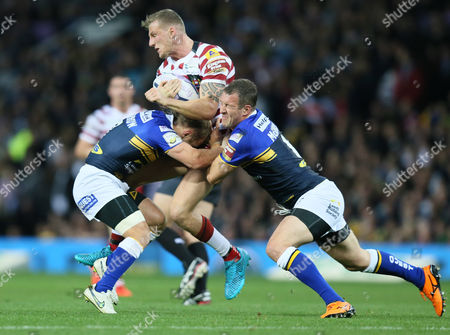 Wigan Warriors Dominic Manfredi is tackled by Leeds Rhinos Rob Burrow and Danny McGuire during the First Utility Super League Grand Final between Leeds Rhinos and Wigan Warriors played at Old Trafford, Manchester, on October 10th 2015