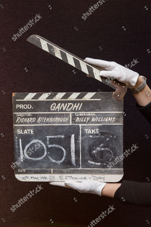 A member of staff from Bonhams holds a clapperboard from the film 'Gandhi' (£2,000-£3,000)