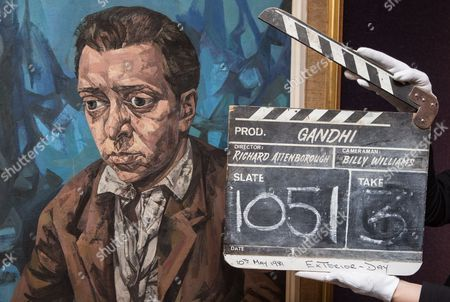 A member of staff from Bonhams holds a clapperboard from the film 'Gandhi' (£2,000-£3,000) alongside a portrait of Attenborough by Bryan Kneale (£2,000-£3,000)