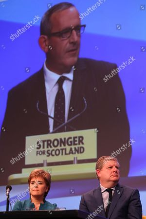 Nicola Sturgeon MSP, Party Leader and First Minister of Scotland, and Angus Robertson MP (Moray), SNP Westminster Group Leader in front of a projection of Stewart Hosie MP (Dundee East), Depute Leader of the SNP and SNP Westminster Group Leader (Economy)