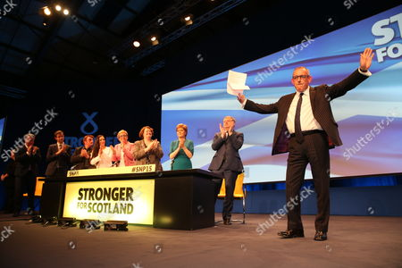 Stewart Hosie MP (Dundee East), Depute Leader of the SNP and SNP Westminster Group Leader (Economy), waves after addressing conference, while applauded by fellow SNP politicians including Nicola Sturgeon MSP, Party Leader and First Minister of Scotland, and Angus Robertson MP (Moray), SNP Westminster Group Leader