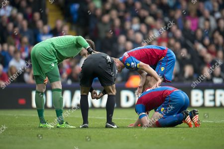 Referee Mark Clattenburg, Goalkeeper Wayne Hennessey and Brede Hangeland of Crystal Palace check on Scott Dann of Crystal Palace during the Barclays Premier League match between Crystal Palace and West Ham United played at Selhurst Park, London on October 17th 2015