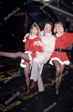 Max Bygraves dancing with two models in Santa outfits