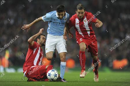 Benoit Tremoulinas & Grzegorz Krychowiak of Sevilla battle for the ball with Jesus Navas of Manchester City during Manchester City vs Sevilla at the Etihad Stadium, Manchester