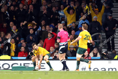 Adam Ashley-Cooper of Australia looks up at Referee: Wayne Barnes  as he touches down for his 3rd try and crucially giving Australia breathing space in the final 10 minutes