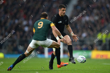 Dan Carter of New Zealand chips the ball past Fourie du Preez of South Africa.