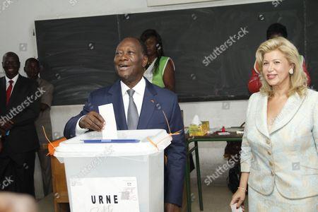 President Alassane Ouattara and wife Dominique Folloroux-Ouattara at a polling station in Abidjan